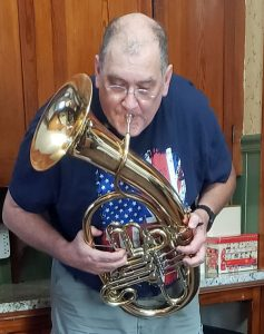 Tren Cheshier playing Wagner tuba at home during lockdown